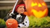 Boy dressed as skeleton holding a plastic sword and a Mickey Mouse pumpkin for trick or treating