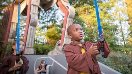 Young Guests dressed as Jedi Knights holding lightsabers outside Star Tours – The Adventures Continue