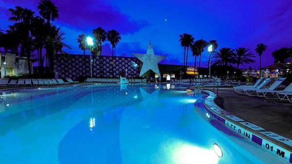 Panoramic view of Grand Slam pool at Disney's All-Star Sports Resort, lit up at night