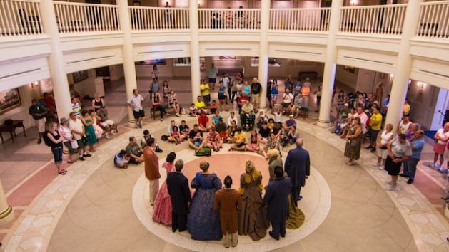 Bird's-eye-view of a rotunda filled with an audience watching a singing group dressed in colonial American dresses and suits