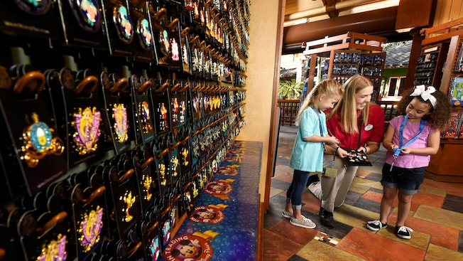 A Cast Member helps 2 little girls pick out pins next to an expansive wall display of pins