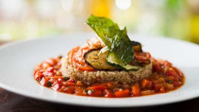 Quinoa garnished with zucchinis, tomatoes and more