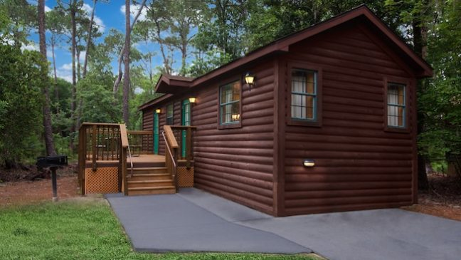 A contemporary log cabin with a raised deck