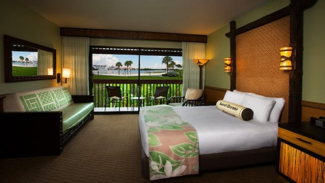 A queen bed across from a daybed and, beyond, a patio and Seven Seas Lagoon