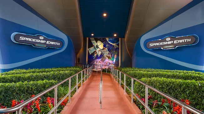 A walkway flanked by 2 wall signs leading up to Spaceship Earth at Epcot
