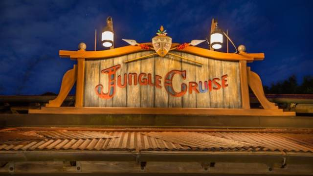 "A wooden engraving that says ""Jungle Cruise"" on top of a building"