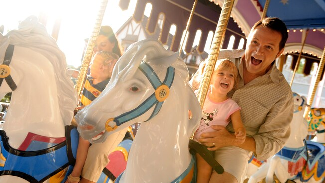 A dad holds his young daughter while riding a horse on Prince Charming Regal Carrousel