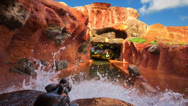 A log heads on a river toward a fallen tree with a beehive overhead at Splash Mountain