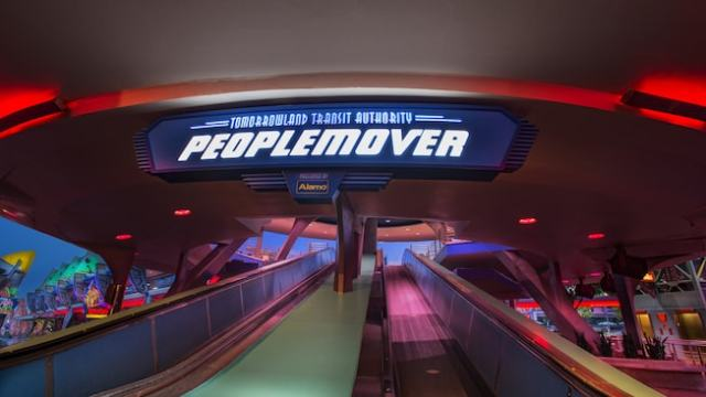 An ascending conveyor belt walkway below a sign to Tomorrowland Transit Authority PeopleMover
