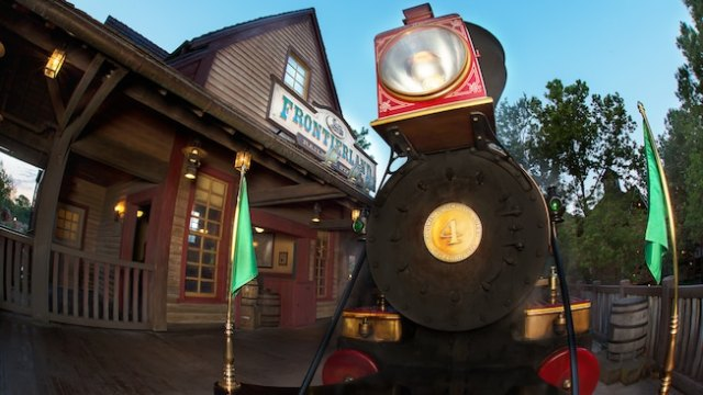 The front of a steam locomotive at the Frontierland Railroad Station at dawn
