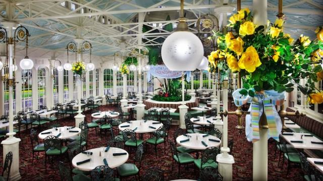 Round tables on the main dining floor, with hanging arrangements of yellow roses