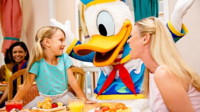 Donald Duck in beach attire greets a young girl and her mother at their breakfast table