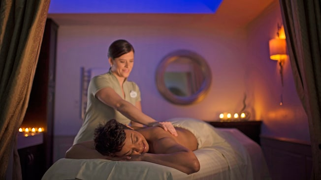A masseuse kneads the shoulder muscles of a woman lying on a massage table