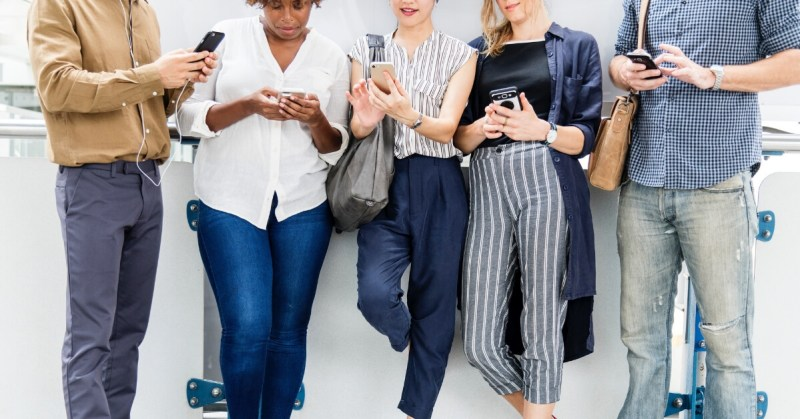 five people leaning against a wall looking down at their phones