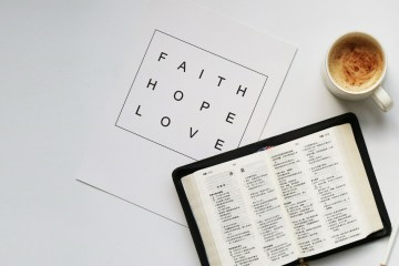 """a bible, cup of coffee and a quote card which reads"""" faith, hope, love"""""""