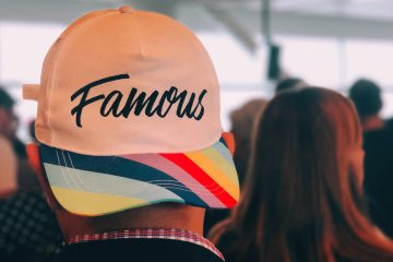 Guy in crowd with modern cap facing backwords reading 'famous'