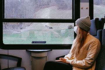 photo of a woman sitting on a train gazing out the window wearing a mask