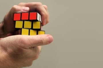 hands working on a rubik cube