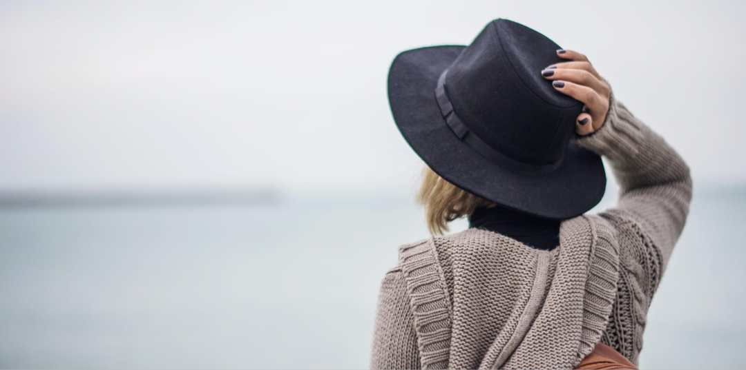 woman holding hat to her head