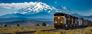 Cargo train moves through Northern California with Mt. Shasta in the background.