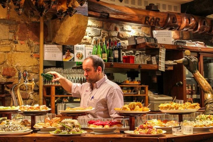 Bartender pours glass of wine at Bar La Cepa in San Sebastian, Spain