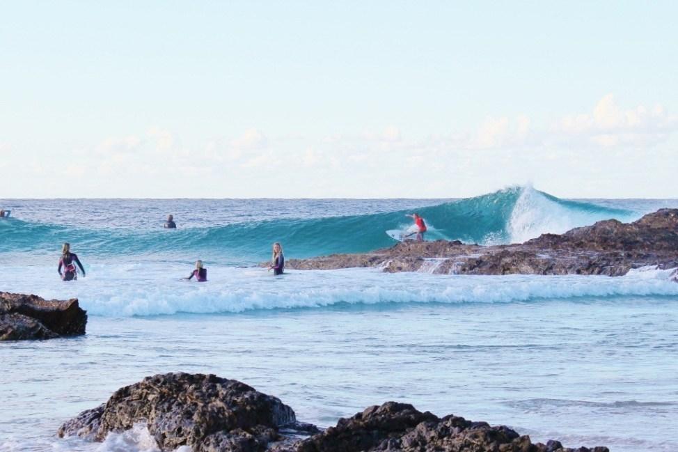 Surfer rides waves at Snapper Rocks in Coolangatta, Gold Coast, Australia