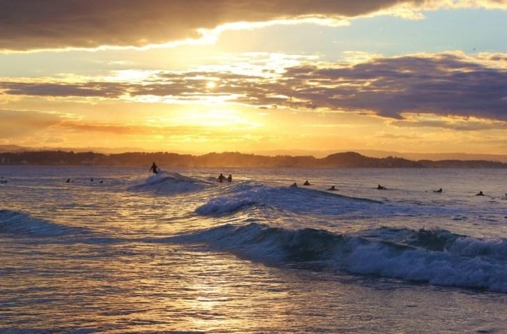 Surfers ride waves at sunset in Coolangatta, Gold Coast, Australia