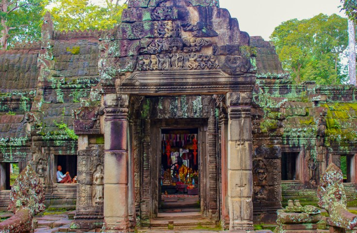 Monk sits in window beside shrine at Banteay Kedi Temple at Angkor Park in Siem Reap, Cambodia