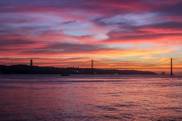 Cristo Rei Lisbon and April 25 Bridge at Sunset in Lisbon, Portugal