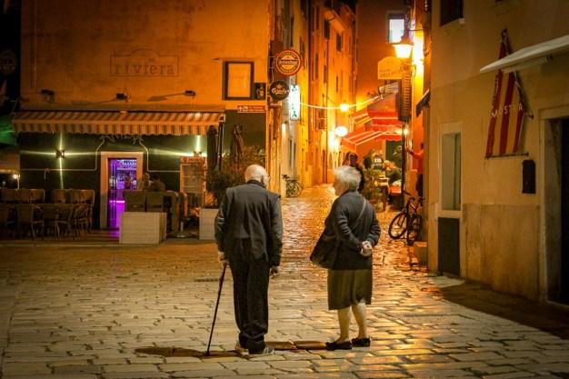 Elderly couple walks on cobblestone lanes in Old Town Rovinj, Croatia