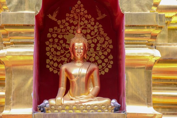 Buddha statue in niche of stupa at Pan On Temple in Chiang Mai, Thailand