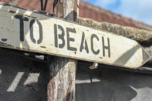 White and black beach sign in Uluwatu, Bali, Indonesia