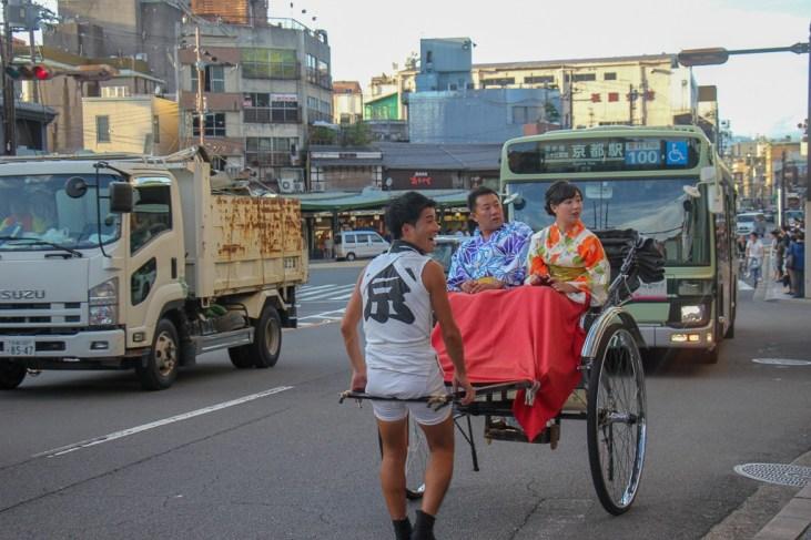 Couple rides in rickshaw in traffic in Kyoto, Japan