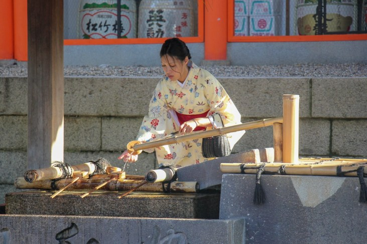 Girls washes hands at temple in Kyoto, Japan