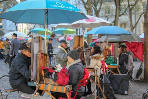 Tourists pose for portrait drawings by artists in Place du Tertre in Montmartre, Paris, France