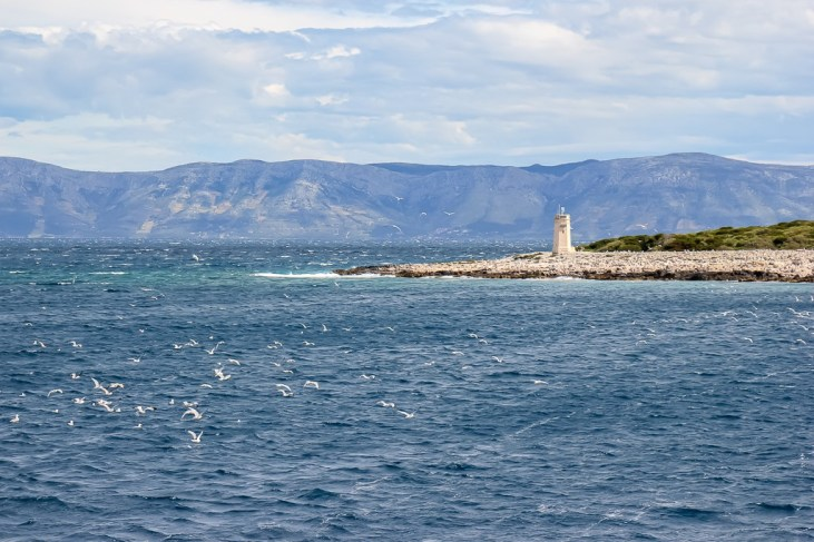 Lighthouse and seagulls on sea near Vela Luka, Korcula Island, Croatia