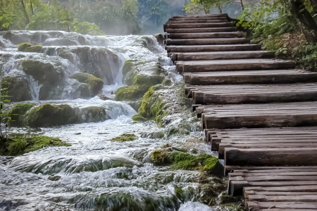 Tumbling waterfall next to wood steps at Plitvice Lakes NP in Croatia
