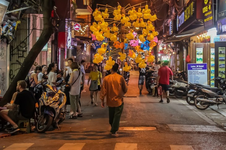 Man sells duck balloons on street in Hanoi, Vietnam