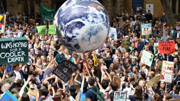 Youth Protestors holding up signs and a big balloon in the image of the earth.