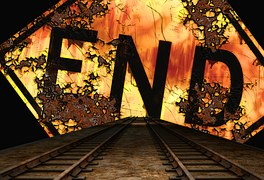 """the word """"End"""" written in black against a tropical sunset scene at the end of railroad tracks."""