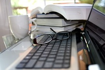 Books, a coffe cup, eyeglasses on a keyboard and a part of a computer screen to signify Online Business
