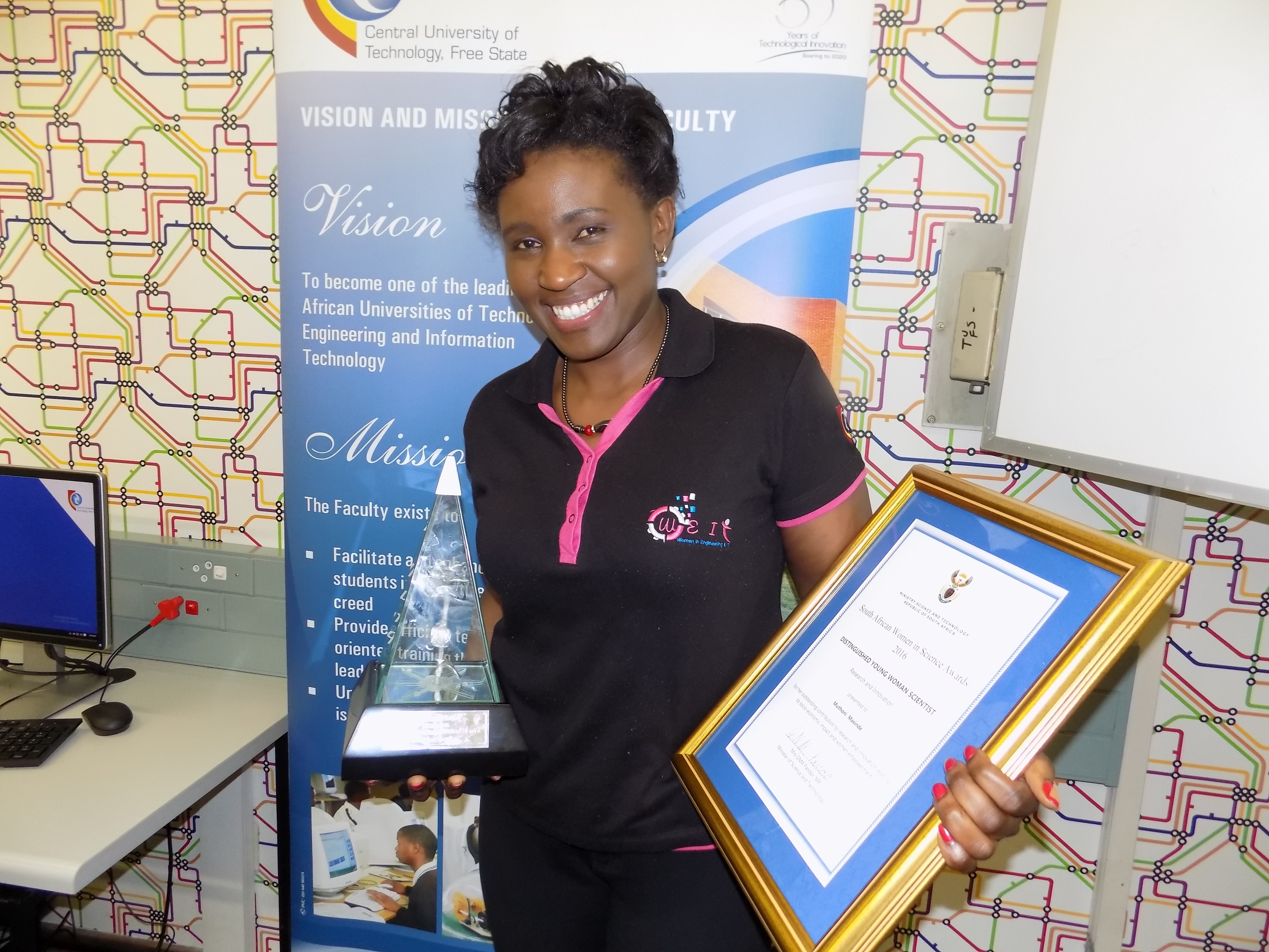 Dr. Muthoni Masinde with trophy and certificate