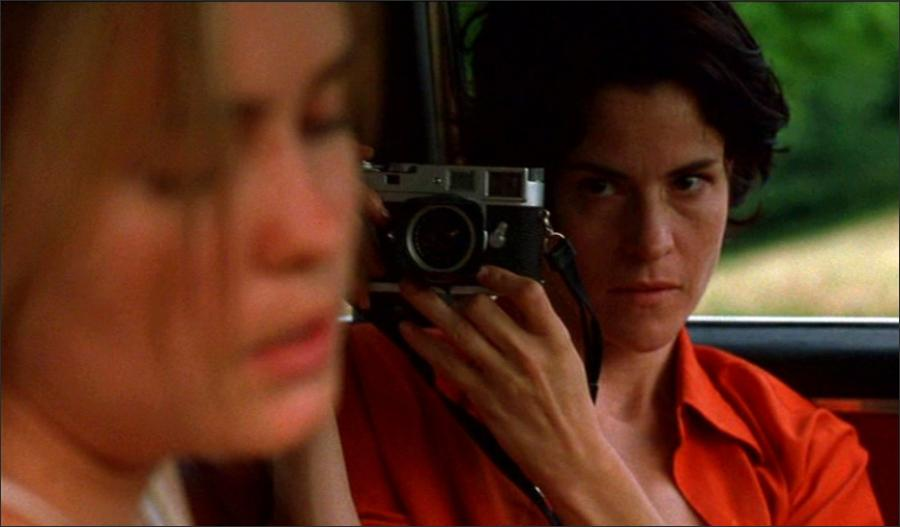 Still from High Art (1998). Syd and Lucy are sat side by side in a car. Syd looks away from Lucy and gazes down, as Lucy aims her camera at Syd's face in close-up.