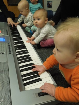 Infants playing a real piano during a unit on music.