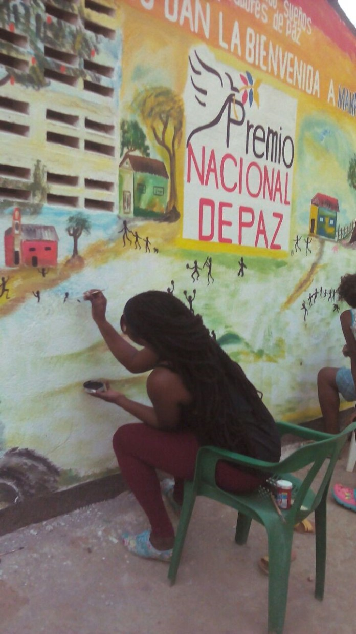 Helping to paint a mural