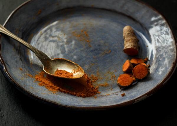 curcuma frais et en poudre sur une assiette bleu