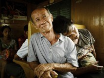 A man falls asleep on the shoulders of another passenger on the train in Bangkok