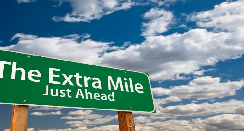 The Extra Mile Just Ahead Green Road Sign Over Dramatic Clouds And Sky.