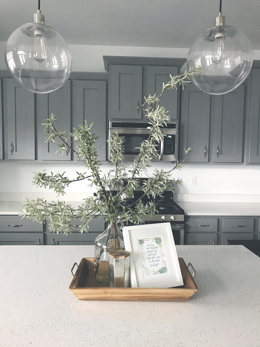 branches make the perfect, tall, dramatic centerpiece for gray cabinet, modern-style kitchen