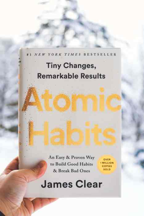 hand holding a hardcover copy of Atomic Habits